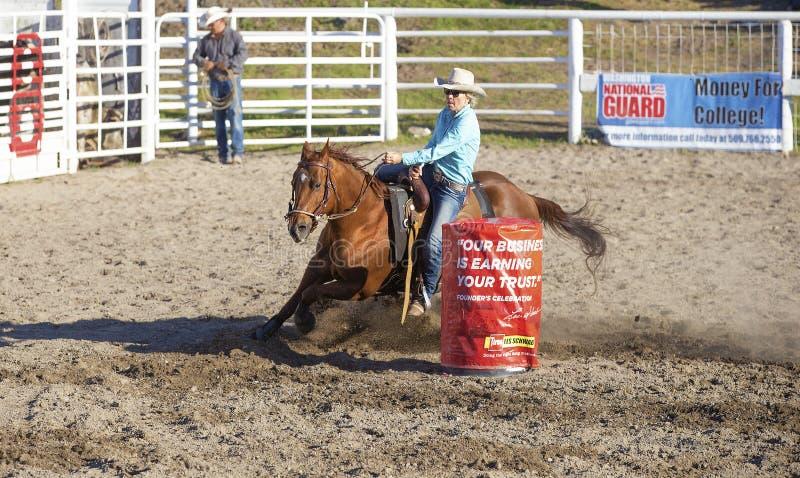 Cow-girls concurrençant dans l'équitation de baril photographie stock libre de droits