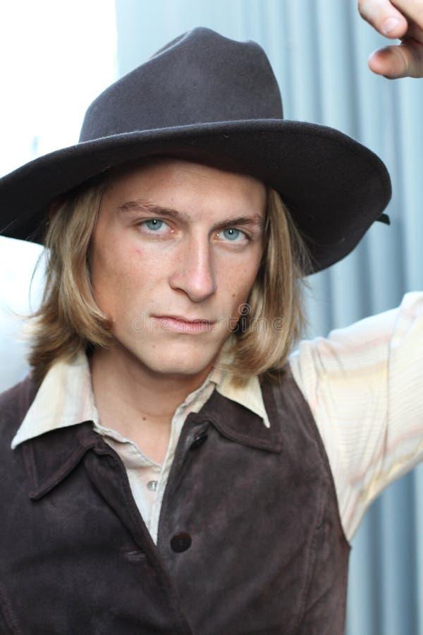Cowboy avec un chapeau regardant sévèrement l'appareil-photo photographie stock libre de droits