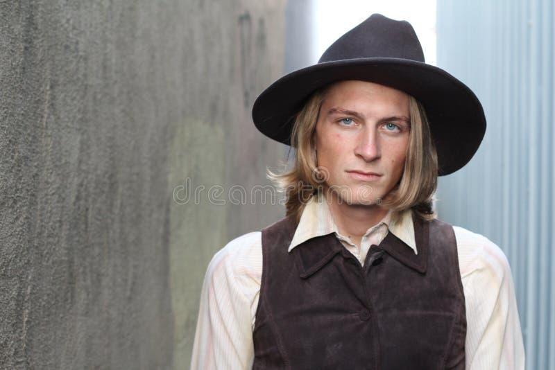 Cowboy avec un chapeau regardant sévèrement l'appareil-photo avec l'espace de copie images libres de droits