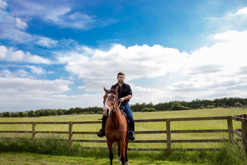Cowboy beau, cavalier de cheval sur la selle, à cheval bottes d'ADN photographie stock
