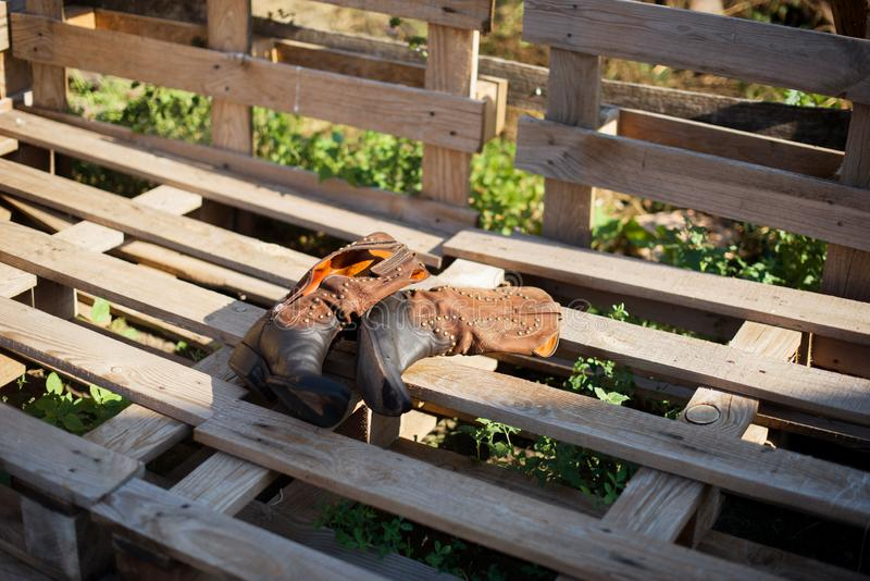 Cowboy boots on a ranch. Wood pallets. Farm stock photos