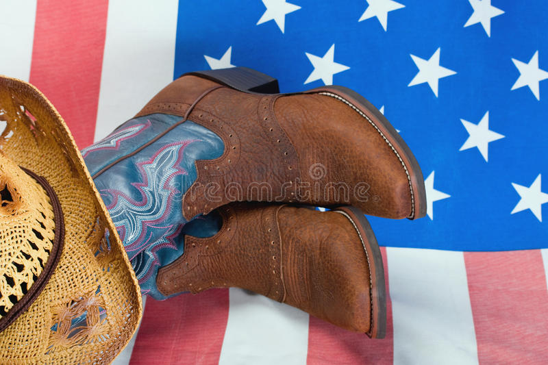 Cowboy boots and straw hat stock image