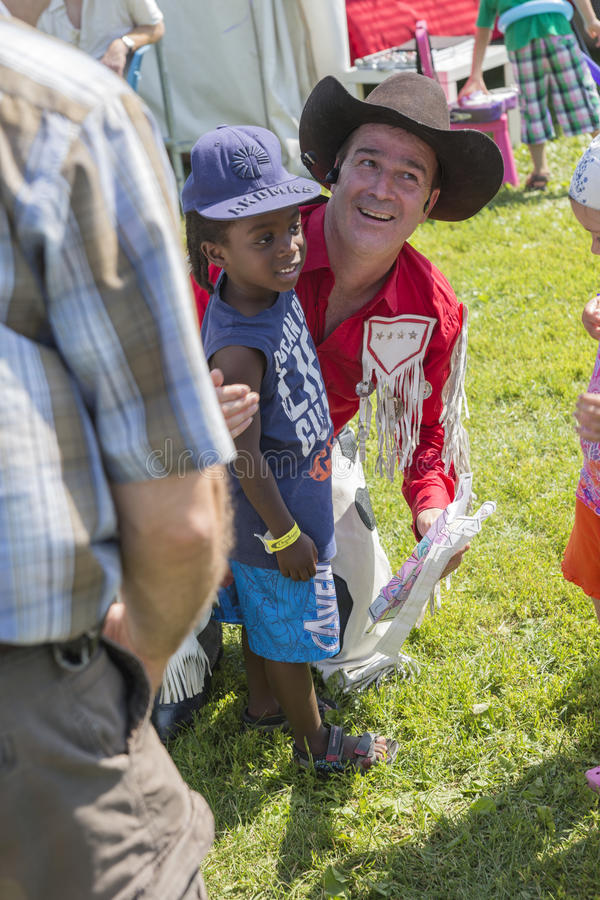 Cowboy with boy. Dan Coboy with children fan during woodstock family event the 5-6 july at ste-julie, quebec, canada royalty free stock images