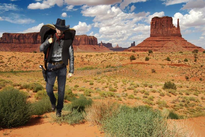 Cowboy che attraversa il deserto immagini stock