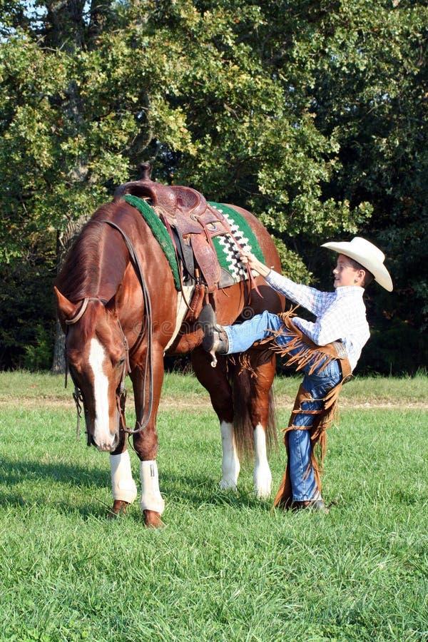 Cowboy che monta il suo cavallo fotografia stock libera da diritti