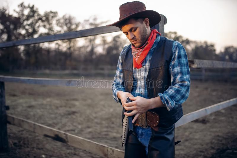 Cowboy checks revolver before gunfight on ranch. Cowboy checks his revolver before gunfight on ranch, western. Vintage male person with gun on farm, wild west royalty free stock photography