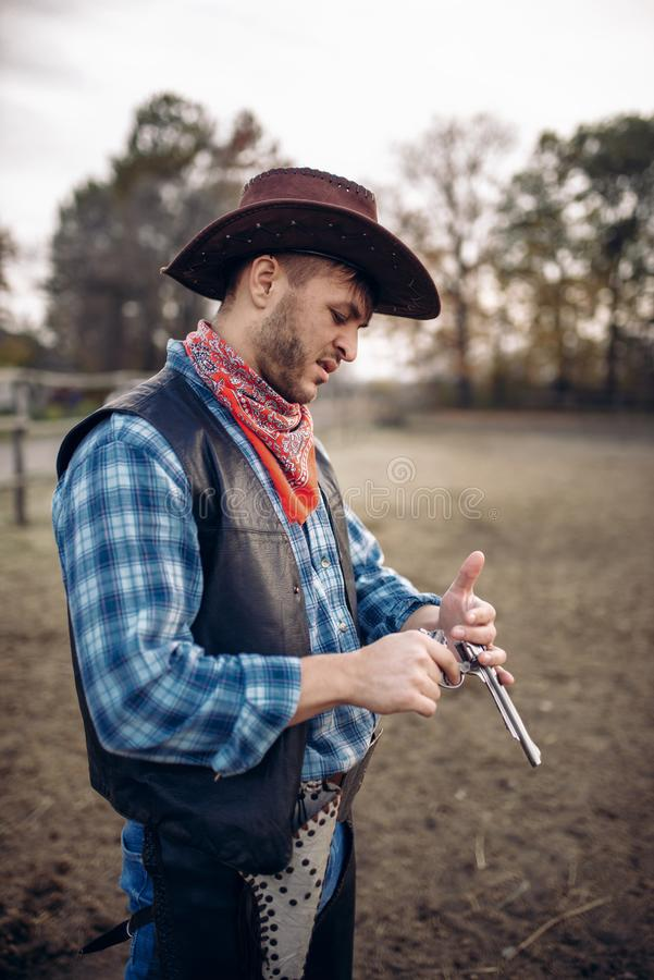 Cowboy checks revolver before gunfight on ranch. Cowboy checks his revolver before gunfight on ranch, western. Vintage male person with gun on farm, wild west stock photos