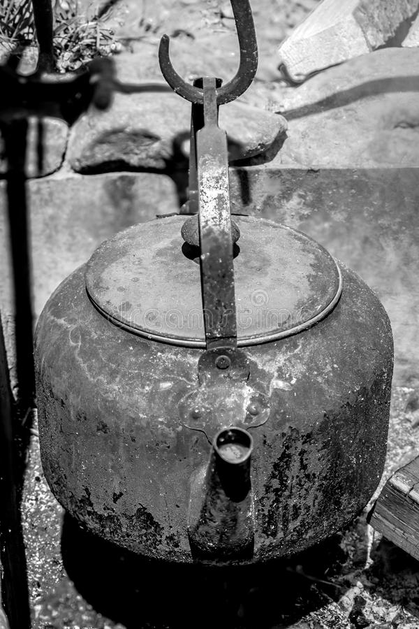 Cowboy Coffee Pot. Fire blackened Coffee kettle hanging in stone fire stock photo