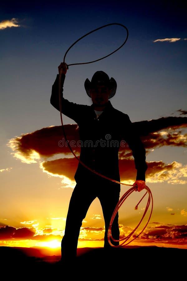 Cowboy com corda no por do sol do ar foto de stock