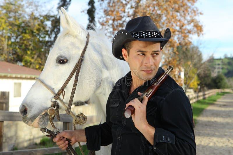 Cowboy con il cavallo bianco e la rivoltella fotografie stock libere da diritti