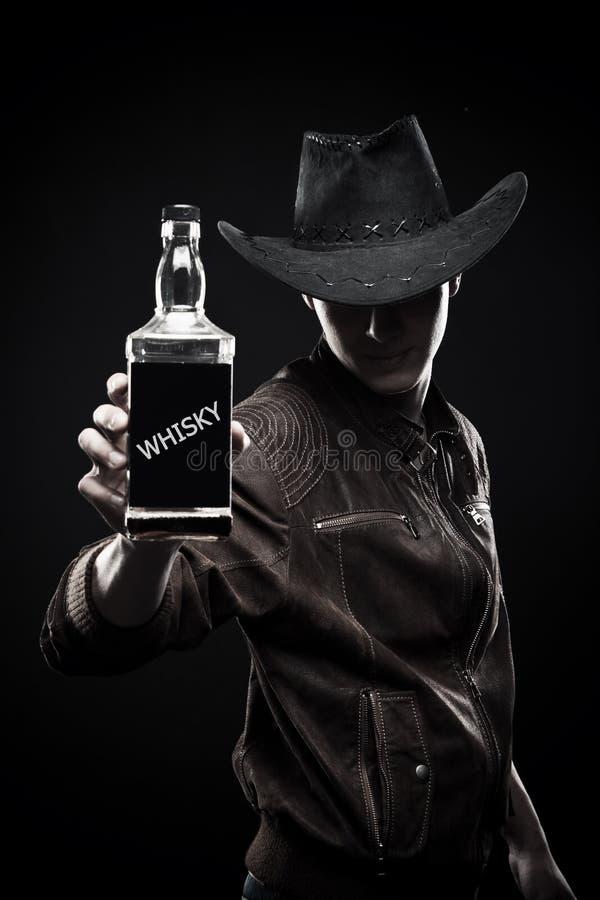 Cowboy con la bottiglia di whiskey fotografie stock libere da diritti