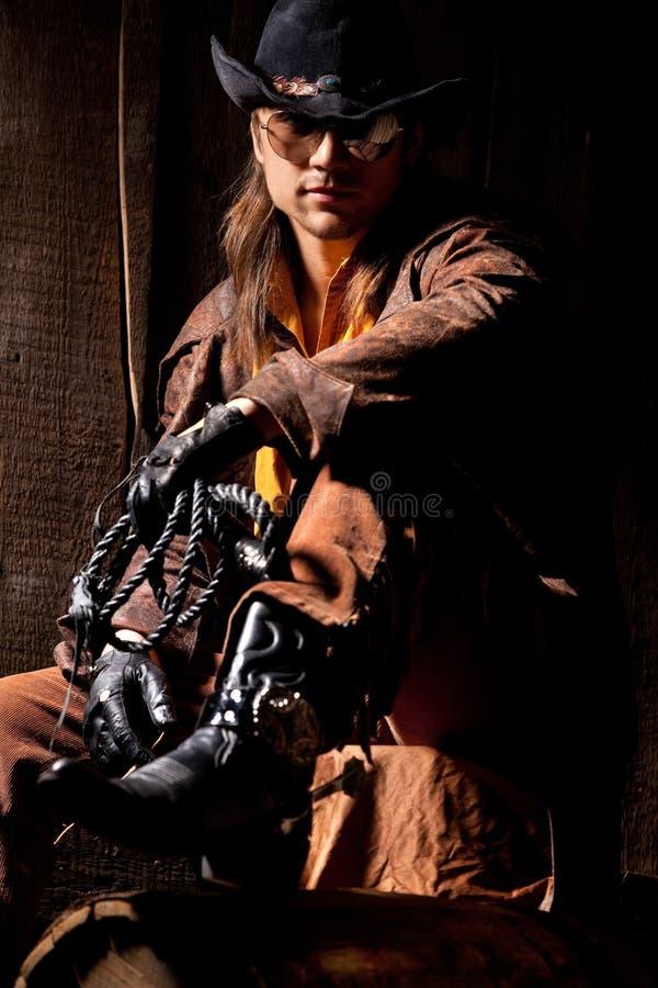 Cowboy con la frusta di cuoio nera di fustigazione immagine stock