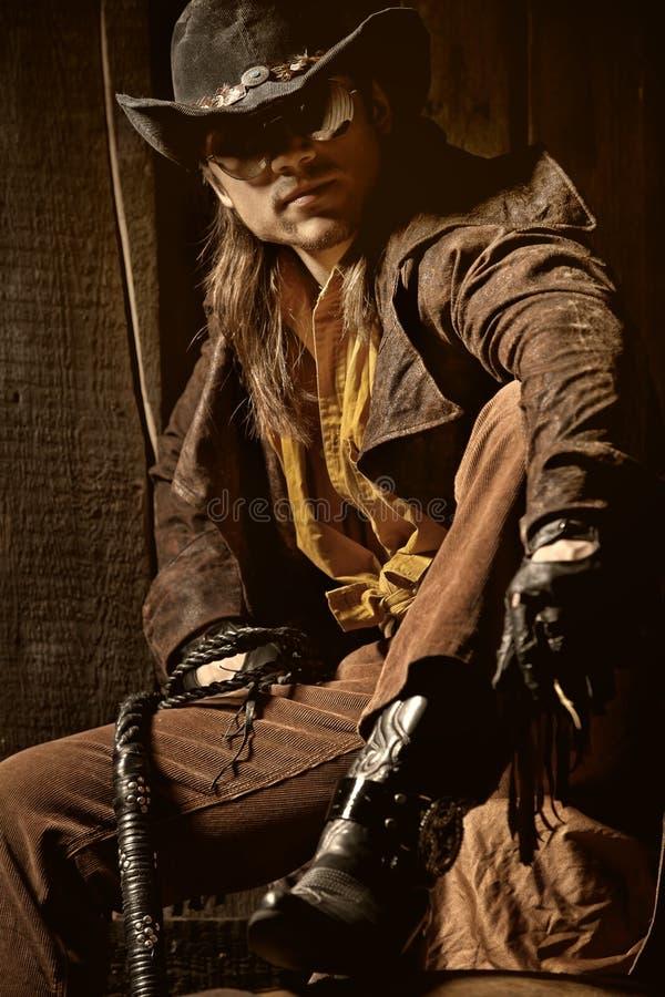 Cowboy con la frusta di cuoio nera di fustigazione fotografia stock libera da diritti