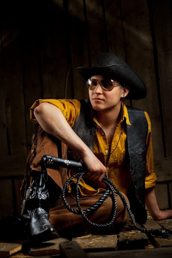 Cowboy con la frusta di cuoio nera di fustigazione immagini stock