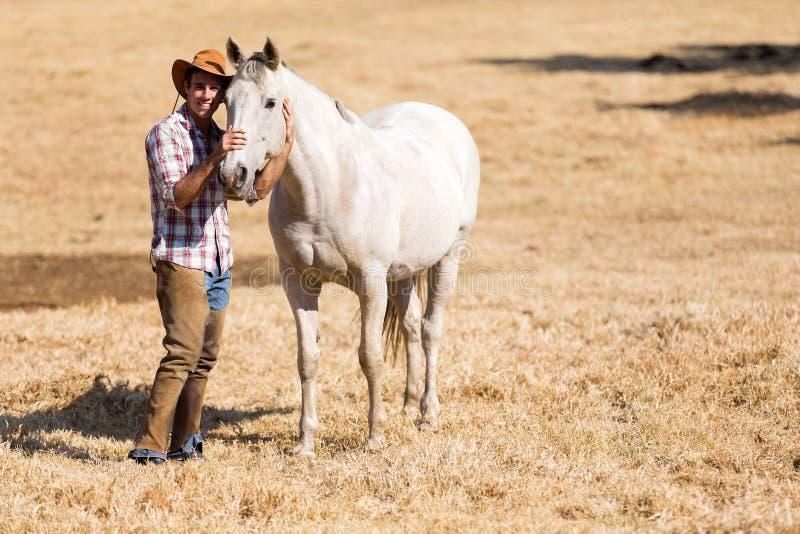 Cowboy con un cavallo bianco immagine stock libera da diritti