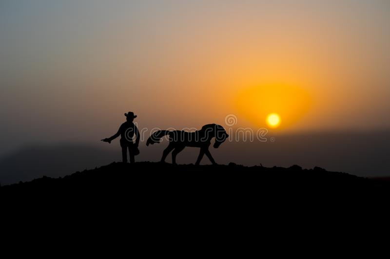 Cowboy concept. Silhouette of Cowboys at sunset time. A cowboy silhouette on a mountain with an yellow sky. Cowboy concept. Silhouette of Cowboy with horse at royalty free stock images