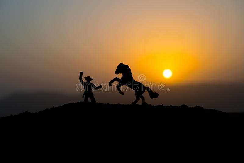 Cowboy concept. Silhouette of Cowboys at sunset time. A cowboy silhouette on a mountain with an yellow sky. Cowboy concept. Silhouette of Cowboy with horse at stock photos