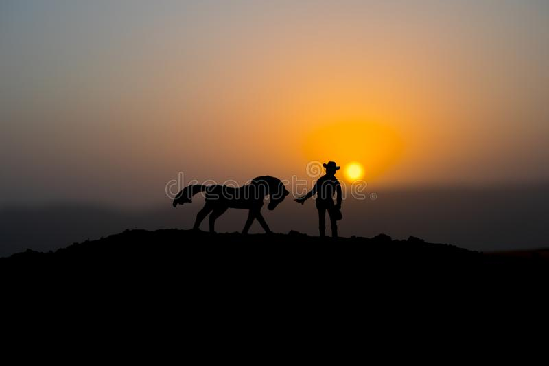 Cowboy concept. Silhouette of Cowboys at sunset time. A cowboy silhouette on a mountain with an yellow sky. Cowboy concept. Silhouette of Cowboy with horse at royalty free stock photos