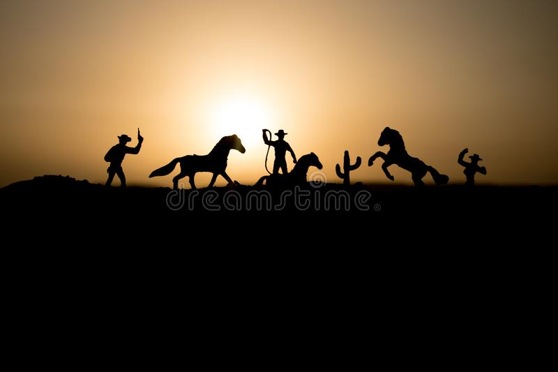 Cowboy concept. Silhouette of Cowboys at sunset time. Cowboys silhouettes on a hill with horses. Selective focus stock photos