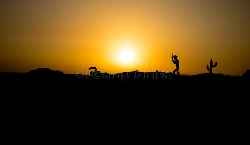 Cowboy concept. Silhouette of Cowboys at sunset time. Cowboys silhouettes on a hill with horses. Selective focus royalty free stock images