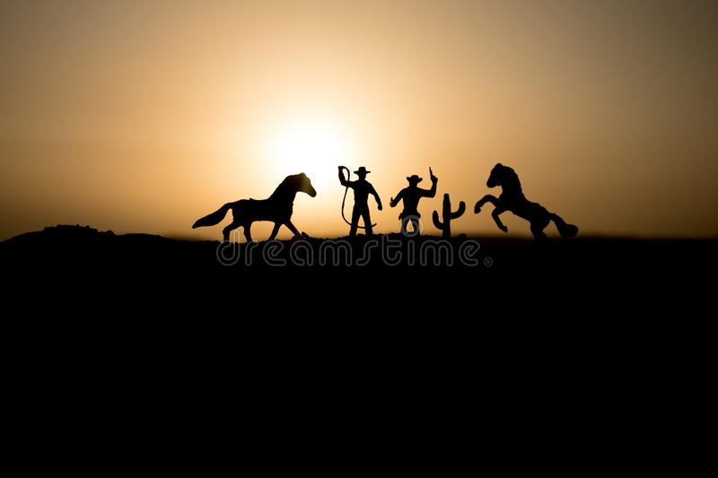 Cowboy concept. Silhouette of Cowboys at sunset time. Cowboys silhouettes on a hill with horses. Selective focus stock photo