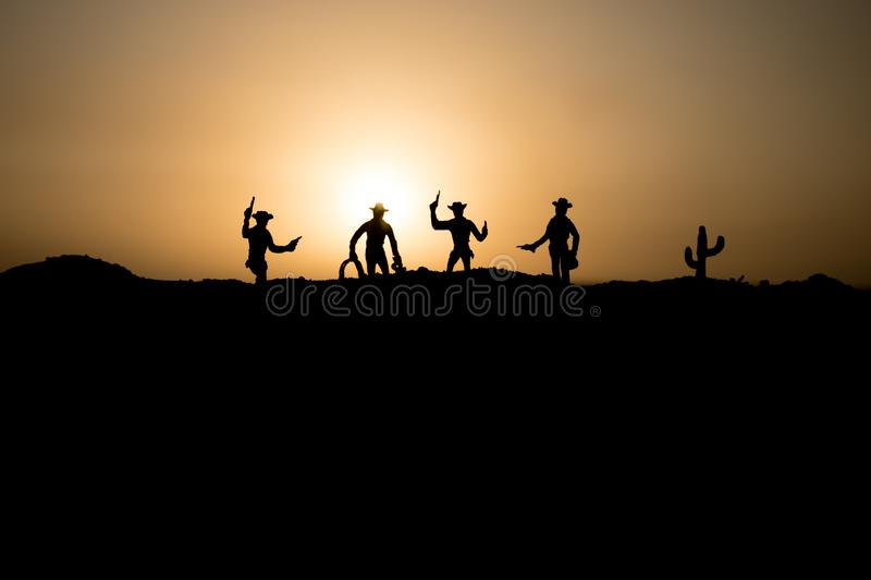 Cowboy concept. Silhouette of Cowboys at sunset time. Cowboys silhouettes on a hill with horses. Selective focus royalty free stock photo
