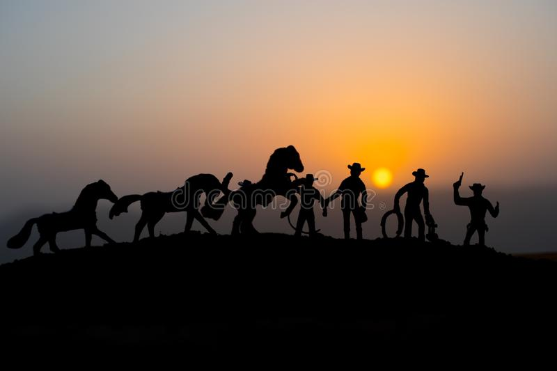 Cowboy concept. Silhouette of Cowboys at sunset time. A cowboy silhouette on a mountain with an yellow sky. Cowboy concept. Silhouette of Cowboys at sunset time stock photo