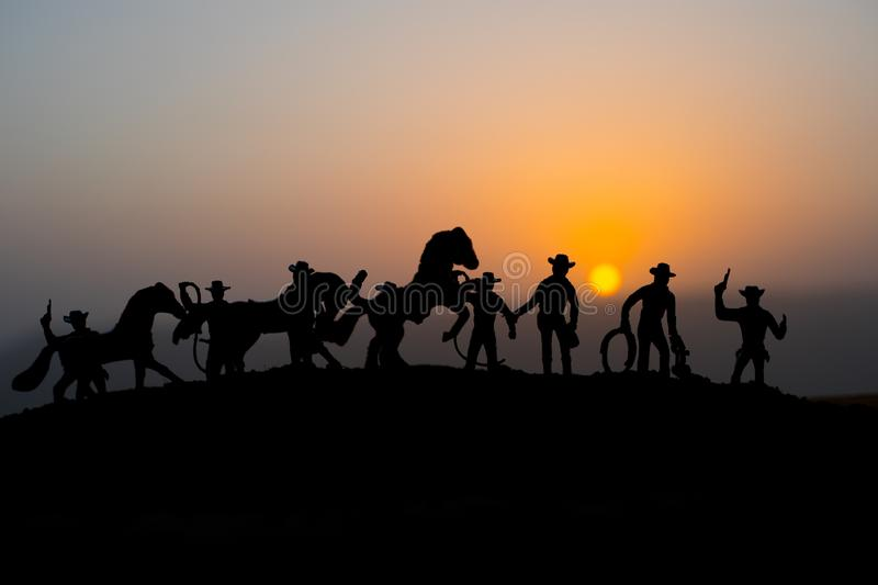 Cowboy concept. Silhouette of Cowboys at sunset time. A cowboy silhouette on a mountain with an yellow sky. Cowboy concept. Silhouette of Cowboys at sunset time royalty free stock image