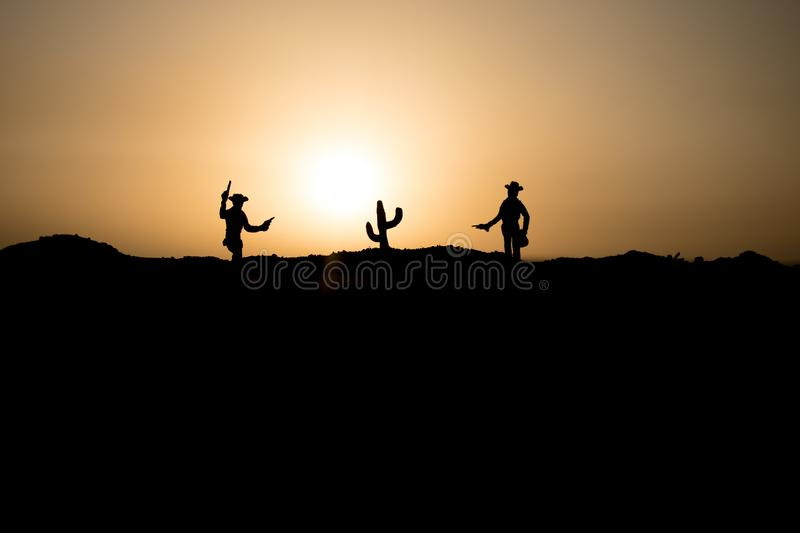Cowboy concept. Silhouette of Cowboys at sunset time. Cowboys silhouettes on a hill with horses. Selective focus royalty free stock image