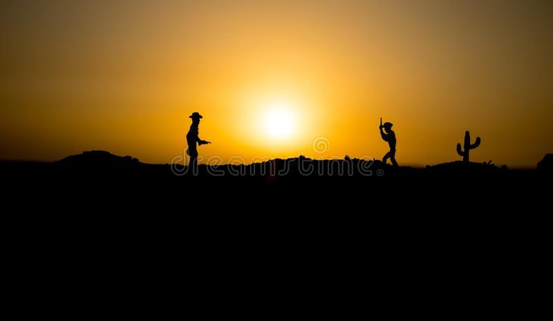 Cowboy concept. Silhouette of Cowboys at sunset time. Cowboys silhouettes on a hill with horses. Selective focus stock photography