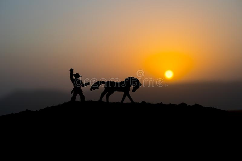 Cowboy concept. Silhouette of Cowboys at sunset time. A cowboy silhouette on a mountain with an yellow sky. Cowboy concept. Silhouette of Cowboy with horse at stock photography