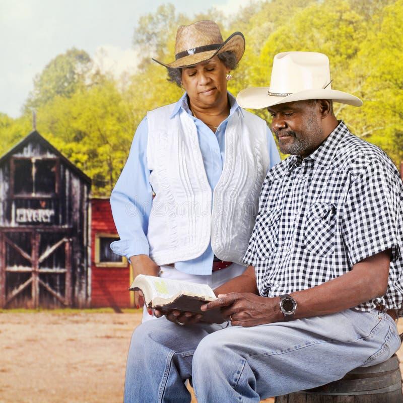 Cowboy Couple de lecture de bible images stock