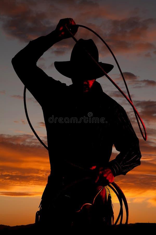 Cowboy dans le coucher du soleil avec la corde images libres de droits
