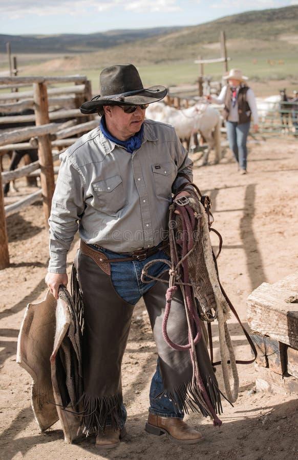 Cowboy de cowboy portant son hackamore, couverture de cheval, corde d'avance et selle à la pièce de pointe photo libre de droits