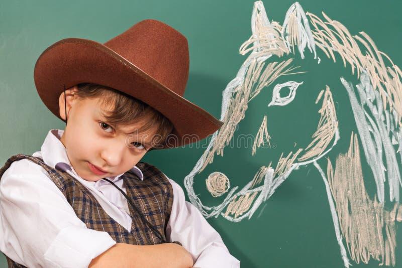 Cowboy dell'artista del ragazzo con un trainato da cavalli da lui fotografia stock