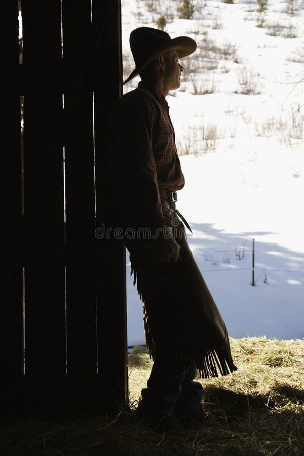 Cowboy, der in der Tür des Stalles sich lehnt stockbild