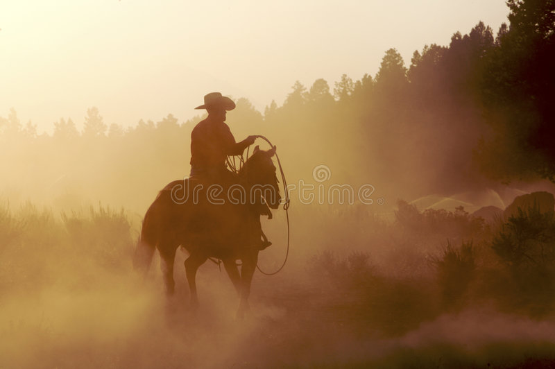 Cowboy in the Dust. Cowboy on his horse walking through dust in the desert