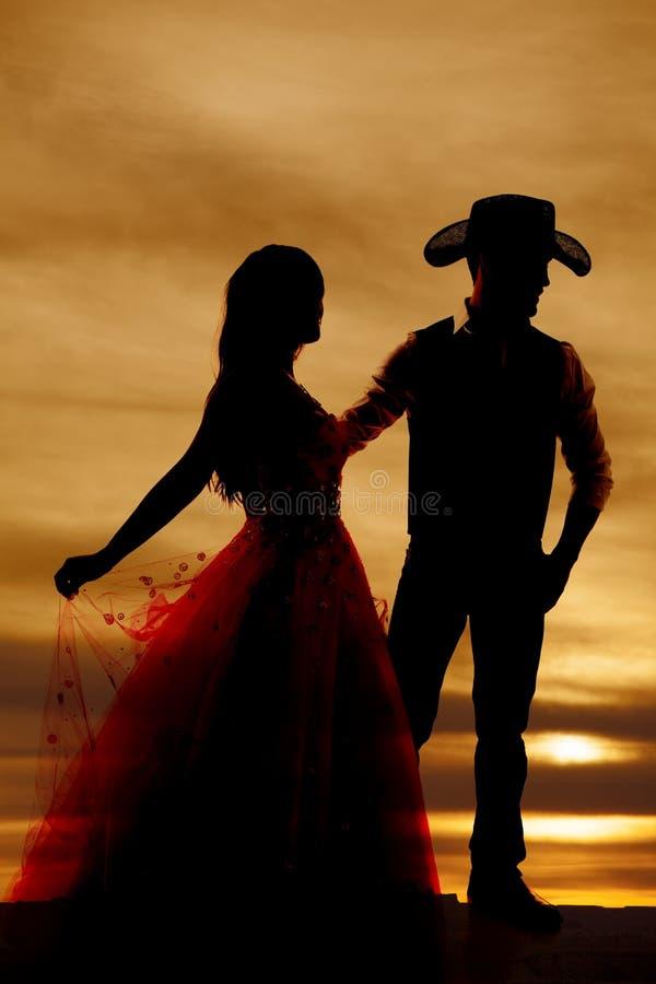 Cowboy e donna della siluetta in vestito immagini stock libere da diritti