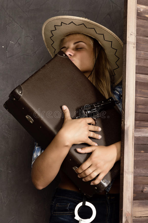 Cowboy girl or pretty woman in stylish hat and blue plaid shirt holding gun and old suitcase royalty free stock images