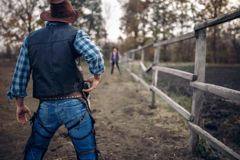 Cowboy with gun prepares to gunfight, back view. Lucky strike on texas ranch, western. Vintage male person with revolver, wild west tradition stock photo