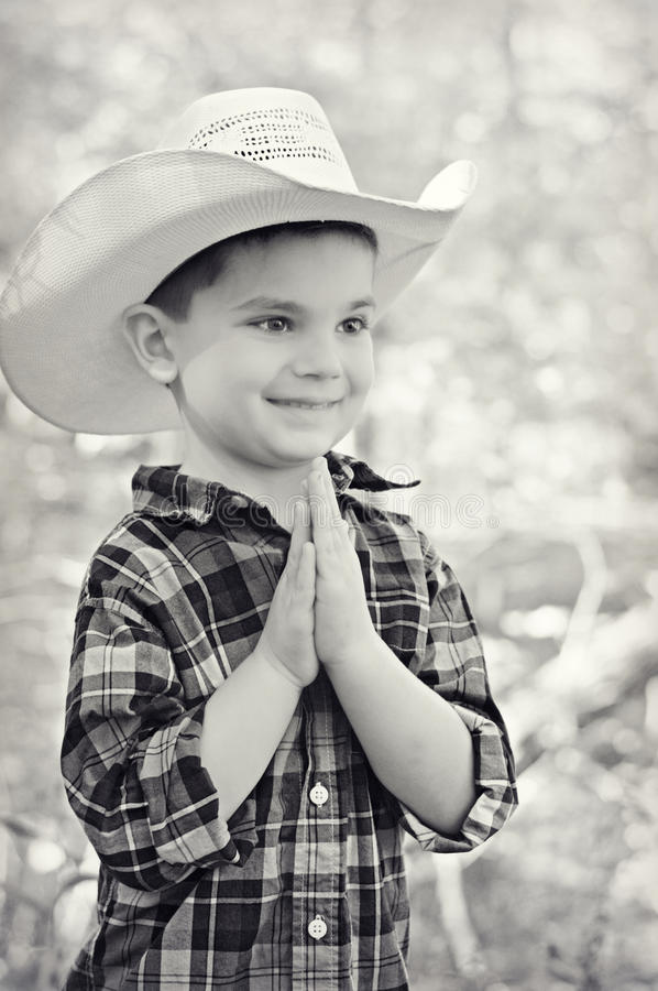 Cowboy Hands Together. A portrait of a young five year old boy dressed like a cowboy plotting his next move. His hands are together and he is smiling thinking of stock photography