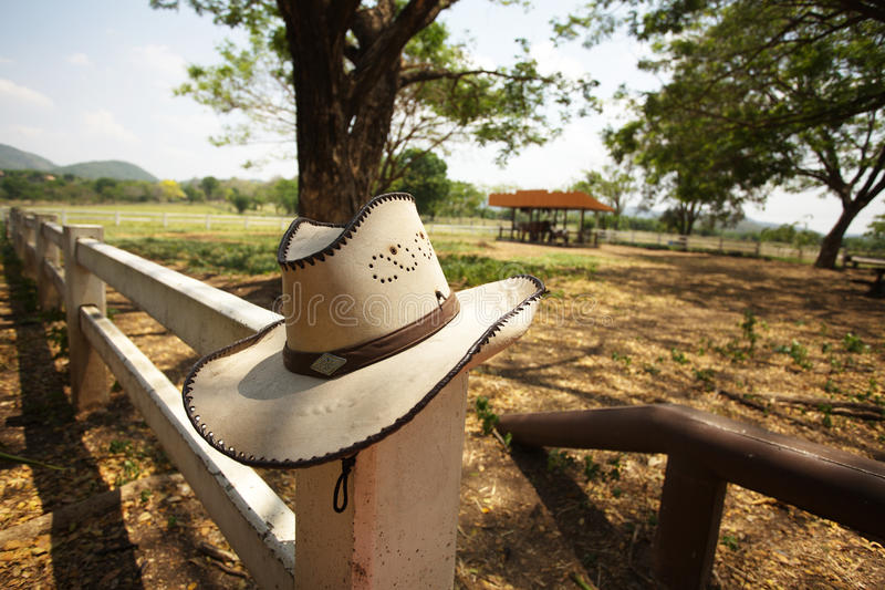 Cowboy hat. Brown cowboy hat hanging on farm fence stock photo