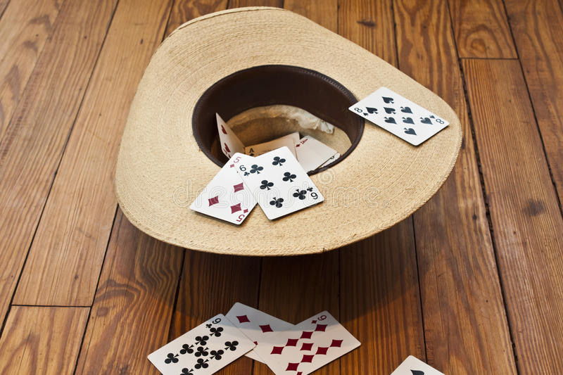 Cowboy hat with cards. Tossing cards into a cowboy hat stock images