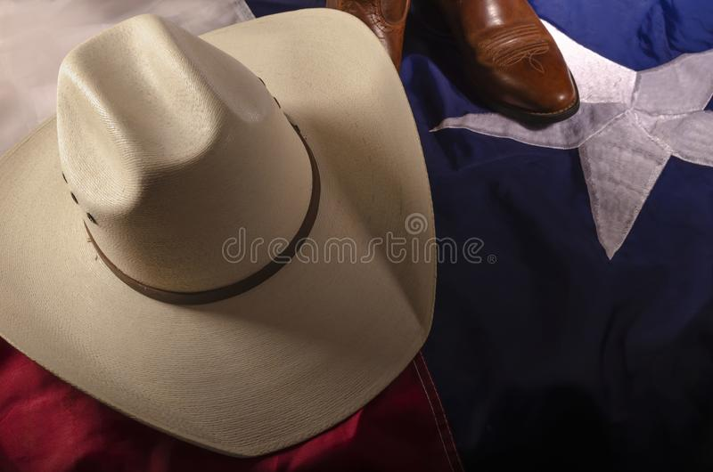 Cowboy hat and Texas flag. A straw cowboy hat covers a pair of western cowboy boots all resting on a Texas flag representing a working lifestyle of the Republic royalty free stock photography