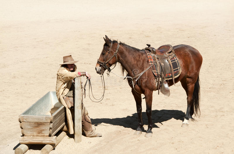 Cowboy and his horse. At a water trough at Mini Hollywood, Almeria, Andalusia, Spain stock images