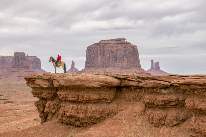 A cowboy and his horse overlook a valley in the Southwest. A cowboy and his horse sitting on a ledge in monument valley enjoying the view stock images