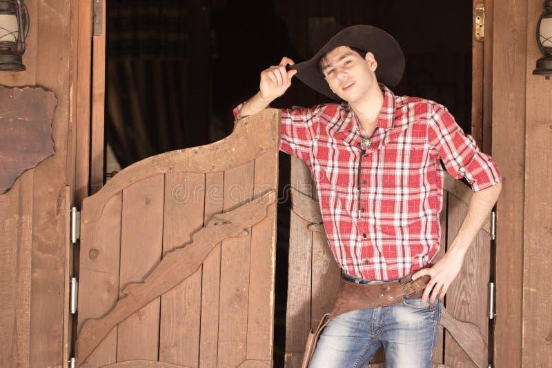 Cowboy in hoed die zich dichtbij zaalingang bevinden stock fotografie