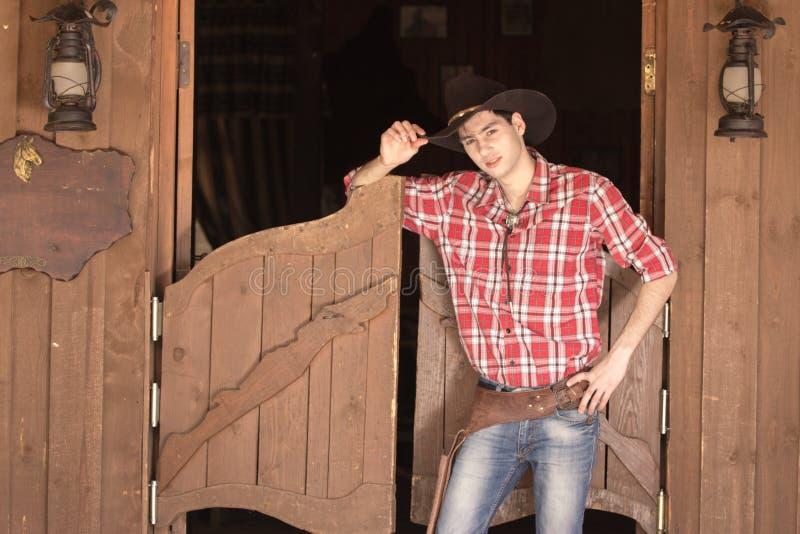 Cowboy in hoed die zich dichtbij zaalingang bevinden stock foto's