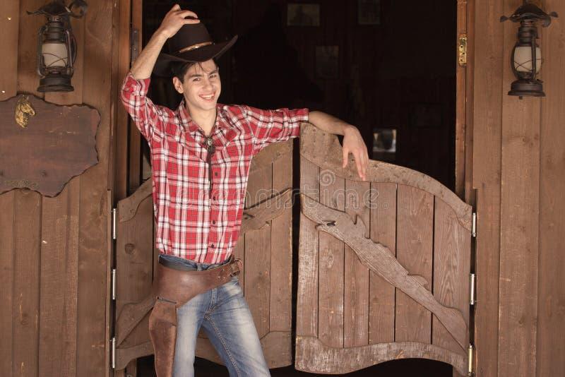 Cowboy in hoed die zich dichtbij zaalingang bevinden stock afbeeldingen