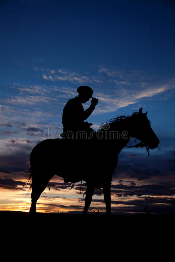 Cowboy holding hat horse sunset. A cowboy is sitting on his horse in the sunset holding his hat stock photos